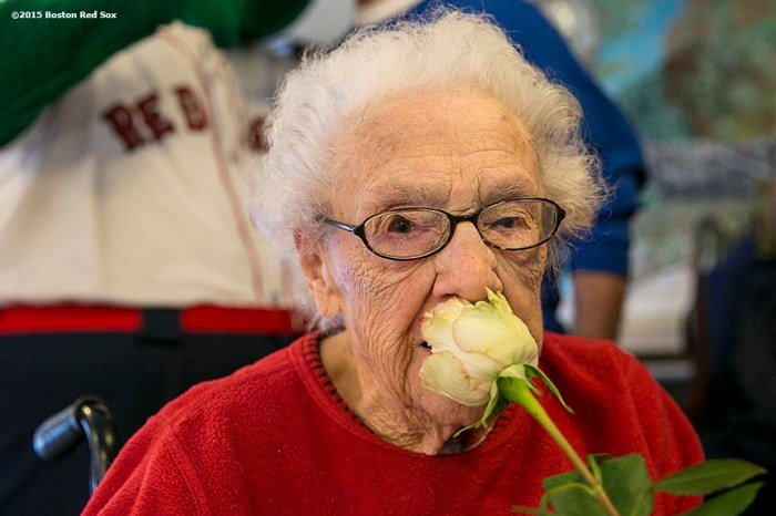 """A resident poses for a photograph with a rose during a Boston Red Sox Valentine's Day caravan to retirement and assisted living communities throughout greater Boston Friday, February 13, 2015."""