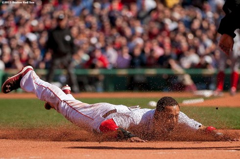 """Boston Red Sox center fielder Mookie Betts dives into third base during the first inning of a home opening game against the Washington Nationals Monday, April 13, 2015 at Fenway Park in Boston, Massachusetts."""