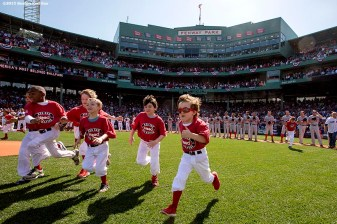 """Kids run onto the field during a pre-game ceremony before the Boston Red Sox 2015 home opener against the Washington Nationals Monday, April 13, 2015 at Fenway Park in Boston, Massachusetts."""