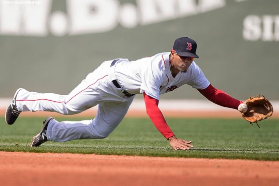 """Boston Red Sox shortstop Xander Bogaerts dives to stop a ground ball during the third inning of a game against the Baltimore Orioles at Fenway Park in Boston, Massachusetts Sunday, April 19, 2015."""