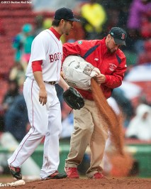 """A member of the grounds crew pours dirt as Boston Red Sox pitcher Junichi Tazawa warms up during the seventh inning of a game against the Baltimore Orioles at Fenway Park in Boston, Massachusetts Monday, April 20, 2015."""