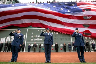 """The American flag is dropped over the Green Monster in honor of Patriot's Day before a game between the Boston Red Sox and the Baltimore Orioles at Fenway Park in Boston, Massachusetts Monday, April 20, 2015."""