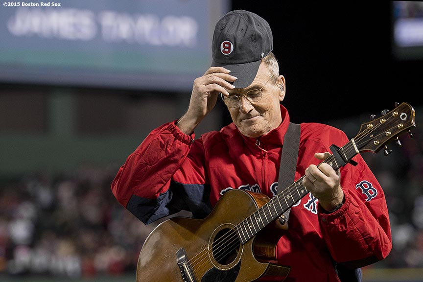 """Singer James Taylor sings 'America The Beautiful' during the seventh inning stretch of a game between the Boston Red Sox and the New York Yankees at Fenway Park in Boston, Massachusetts Sunday, May 3, 2015."""