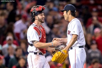 """Boston Red Sox catcher Blake Swihart and pitcher Koji Uehara high five after defeating the Texas Rangers at Fenway Park in Boston, Massachusetts Saturday, May 23, 2015."""