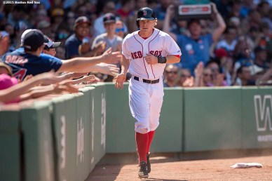 """Boston Red Sox third baseman Brock Holt high fives fans after scoring during the sixth inning of a game against the Los Angeles Angels of Anaheim at Fenway Park in Boston, Massachusetts Sunday, May 24, 2015."""
