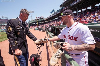 """First Baseman Mike Napoli gives a way pairs of signed cleats to military members before a game between the Boston Red Sox and the Los Angeles Angels Of Anaheim at Fenway Park in Boston, Massachusetts Sunday, May 24, 2015."""