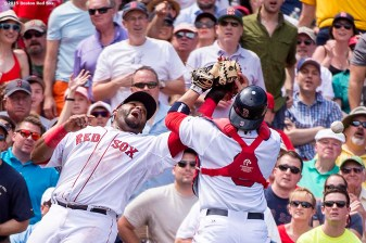 """Boston Red Sox catcher Sandy Leon and third baseman Pablo Sandoval collide while attempting to catch a foul ball during the third inning of a game against the Toronto Blue Jays at Fenway Park in Boston, Massachusetts Saturday, June 13, 2015."""