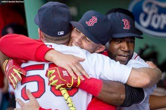 """Boston Red Sox first base coach Brian Butterfield, pitcher Justin Masterson, and designated hitter David Ortiz hug each other before a game against the Baltimore Orioles at Fenway Park in Boston, Massachusetts Wednesday, June 24, 2015."""