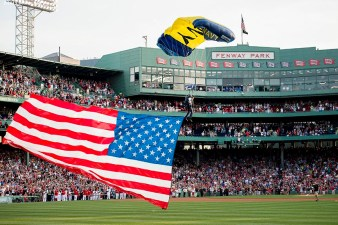 """A member of the US Navy SEAL leapfrog team parachutes into Fenway Park with an American Flag before a game between the Boston Red Sox and the Houston Astros at Fenway Park in Boston, Massachusetts Friday, July 3, 2015."""