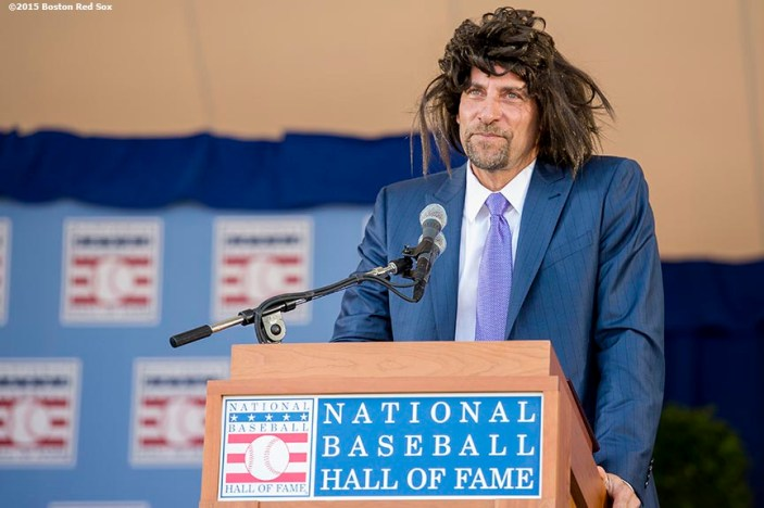 """Class of 2015 Hall of Fame inductee John Smoltz wears a wig as he speaks at the plaque ceremony during the 2015 Hall of Fame weekend at the National Baseball Hall of Fame in Cooperstown, New York Sunday, July 26, 2015."""