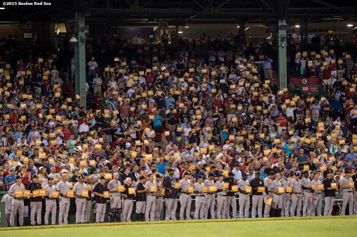 """Members of the New York Yankees hold up signs during a a childhood cancer awareness ceremony during the third inning of a game between the Boston Red Sox and the New York Yankees at Fenway Park in Boston, Massachusetts Tuesday, September 1, 2015."""
