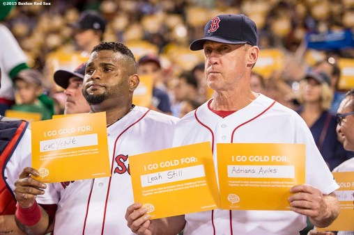 """Boston Red Sox third baseman Pablo Sandoval and third base coach Brian Butterfield hold up signs during a a childhood cancer awareness ceremony during the third inning of a game between the Boston Red Sox and the New York Yankees at Fenway Park in Boston, Massachusetts Tuesday, September 1, 2015."""