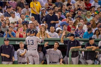 """New York Yankees designated hitter Alex Rodriguez high fives teammates after scoring during the fifth inning of a game against the Boston Red Sox at Fenway Park in Boston, Massachusetts Tuesday, September 1, 2015."""