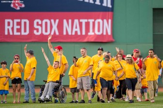 """Cancer survivors walk onto the field during a childhood cancer awareness pre game ceremony before a game between the Boston Red Sox and the New York Yankees at Fenway Park in Boston, Massachusetts Tuesday, September 1, 2015."""