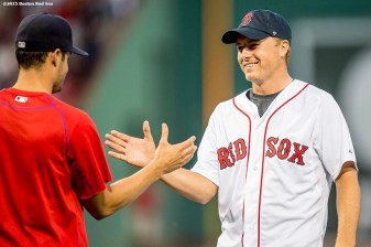 """PGA tour golfer Jordan Spieth high fives Boston Red Sox pitcher Joe Kelly after throwing out the ceremonial first pitch before a game between the Boston Red Sox and the New York Yankees at Fenway Park in Boston, Massachusetts Tuesday, September 1, 2015."""