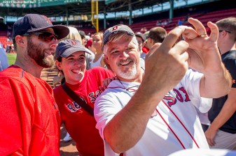 """Boston Red Sox second baseman Dustin Pedroia poses for a selfie photograph with fans during on-field photo day before game against the Philadelphia Phillies at Fenway Park in Boston, Massachusetts Saturday, September 6, 2015."""