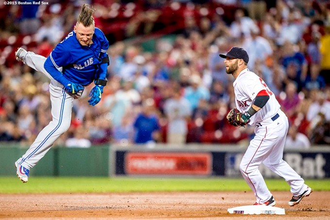 """Boston Red Sox second baseman Dustin Pedroia tags third baseman Josh Donaldson during the first inning of a game against the Toronto Blue Jays at Fenway Park in Boston, Massachusetts Monday, September 9, 2015."""