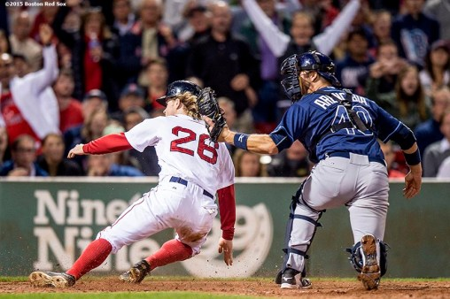 """Boston Red Sox third baseman Brock Holt slides into home plate during the sixth inning of a game against the Tampa Bay Rays at Fenway Park in Boston, Massachusetts Monday, September 21, 2015."""