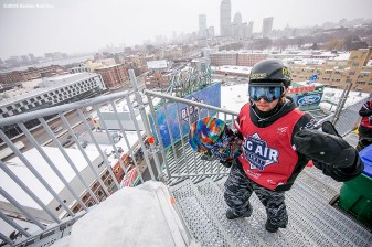 """A snowboarder walks to the top of the ramp during the Polartec Big Air at Fenway ski and snowboard competition at Fenway Park in Boston, Massachusetts Thursday, February 11, 2016."""