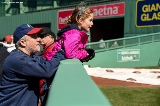 """A fan peeks over the bullpen wall during Little League Opening Day at Fenway Park in Boston, Massachusetts Saturday, April 9, 2016."""