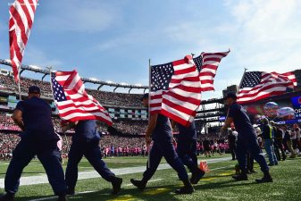 FOXBORO, MA - OCTOBER 16: Members of the military carry American flags before a game between the New England Patriots and the Cincinnati Bengals at Gillette Stadium on October 16, 2016 in Foxboro, Massachusetts. (Photo by Billie Weiss/Getty Images)