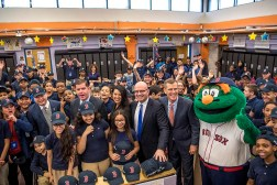 March 27, 2017, Boston, MA: Maria Cordon, Principal of the MIddle School, Boston Public Schools Superintendent Tommy Chang, Boston Mayor Marty Walsh, Linda Pizzuti Henry, wife of Boston Red Sox Principal Owner John Henry, Marty St. George, Executive Vice President, Commercial and Planning, JetBlue, Boston Red Sox President Sam Kennedy, and Boston Red Sox mascot Wally the Grreen Monster pose for a group photograph with students as Red Sox hats are given away during a visit to the Hennigan School in Jamaica Plain, Massachusetts Monday, March 27, 2017. (Photo by Billie Weiss/Boston Red Sox)
