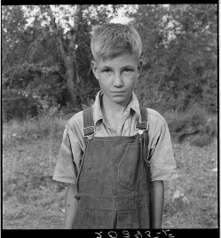 """Migratory boy in squatter camp. Has come to Yakima Valley for the third year to pick hops. Mother: """"You'd be surprised what that boy can pick."""" Washington, Yakima Valley."""