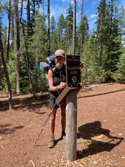 A picture of Katrina signing the trail register at the norther boundary of Crater Lake National Park.