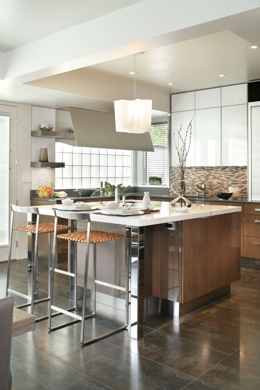 Contemporary kitchen with U-shape d layout features an island with polished stainless legs. Flat panel, frameless, fully custom Artcraft cabinetry is incporated in a mix of quarter-sawn anegre with a silvery finish and a high-gloss custom brown lacquer. Design by Regina Bilotta of Bilotta Kitchens.