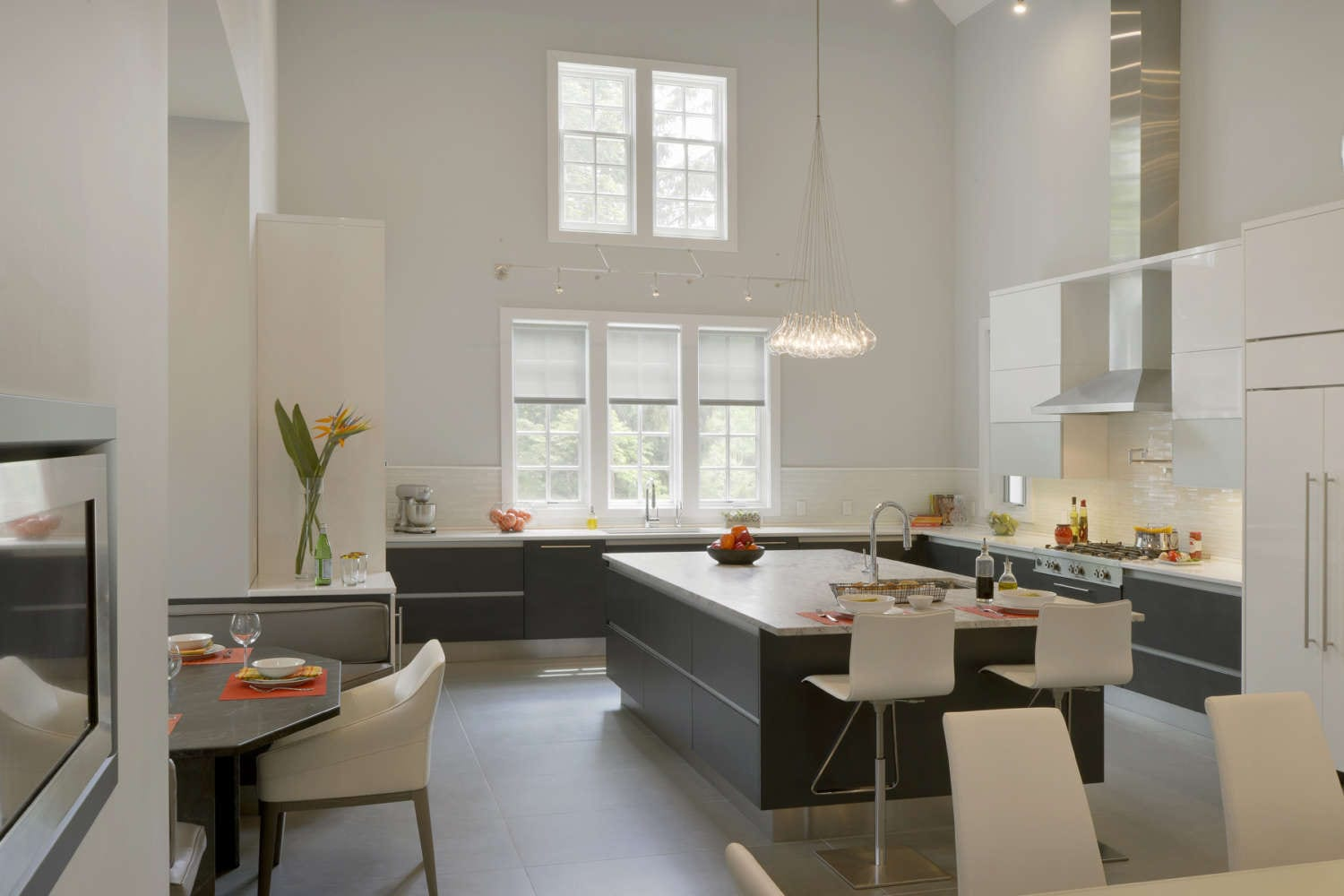 Large, open contemporary kitchen with high ceilings, sculptural blown glass lighting and flat panel, frameless Artcraft Cabinetry in both high-gloss white finish and dark quarter sawn oak veneer. Fully custom cabinets feature alumasteel accents, including an alumasteel toe kick. Design by Aston Smith of Bilotta Kitchens.