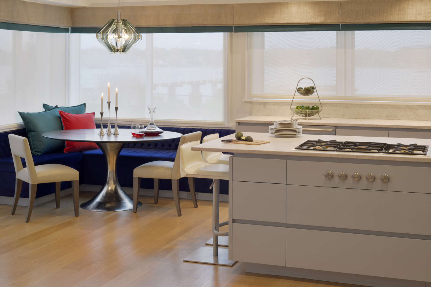 Light contemporary kitchen features flat panel, frameless Bilotta Cabinetry in Benjamin Moore Pigeon Grey, light quartz countertops, and oak hardwood flooring. Banquette area features a tulip table with with seating. Design by Randy O'Kane, CKD, of Bilotta Kitchens.