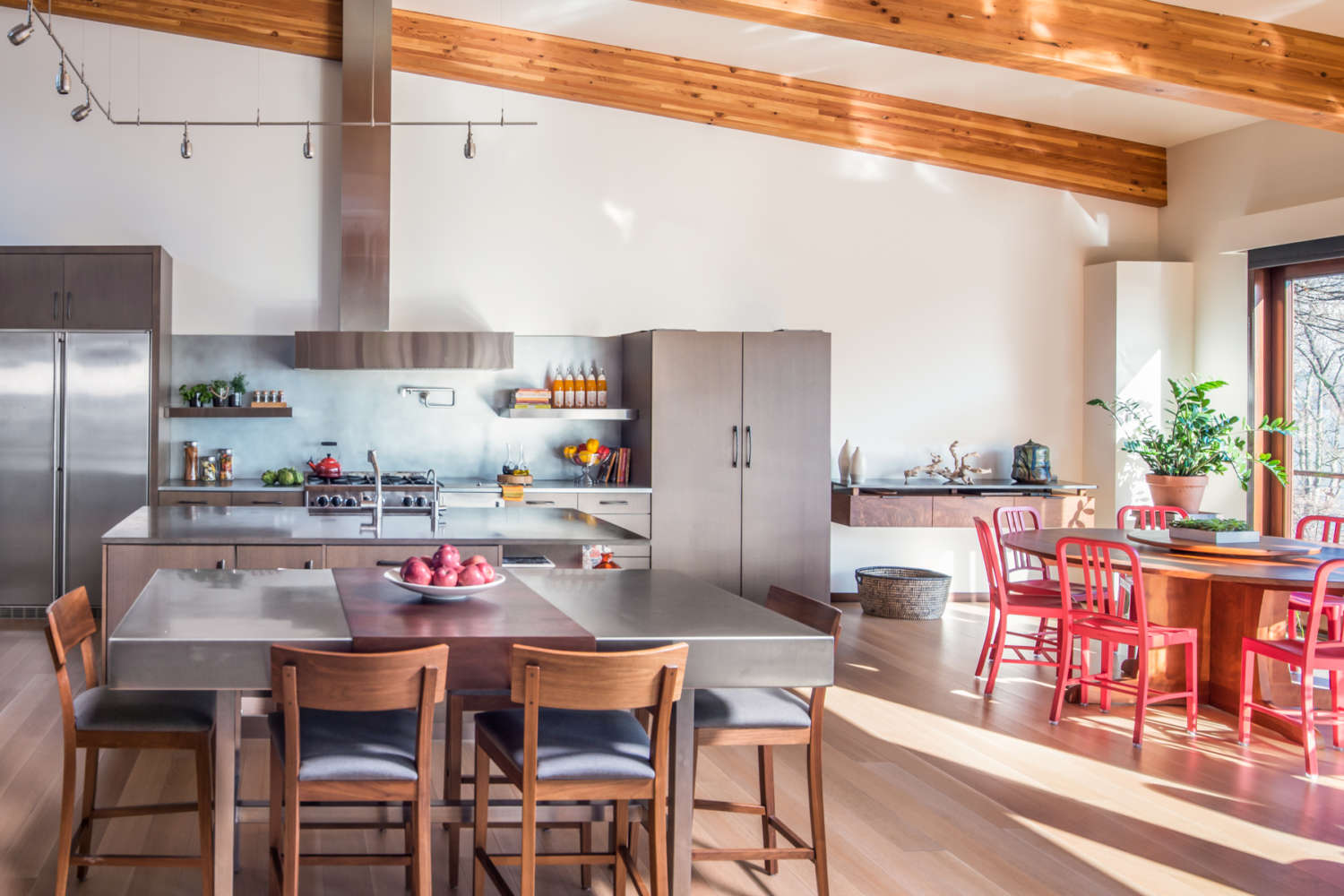Open kitchen with exposed beams features fully custom flat panel, frameless Artcraft Cabinetry in rift cut white oak with smokewood stain. Island and eating area feature brushed stainless surfaces. Design by RitaLuisa Garces of Bilotta Kitchens.