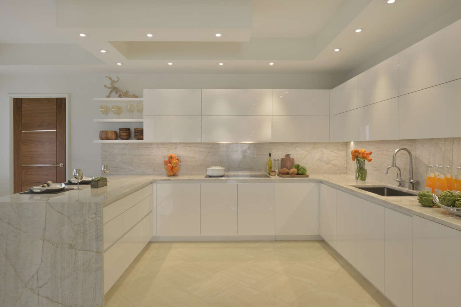 U-shaped kitchen features high gloss white, flat panel fully custom Artcraft cabinetry, light marble countertop and backsplash with veining, light porcelain tile flooring, open shelving and soft lighting. Design by Tabitha Tepe of Bilotta Kitchens.
