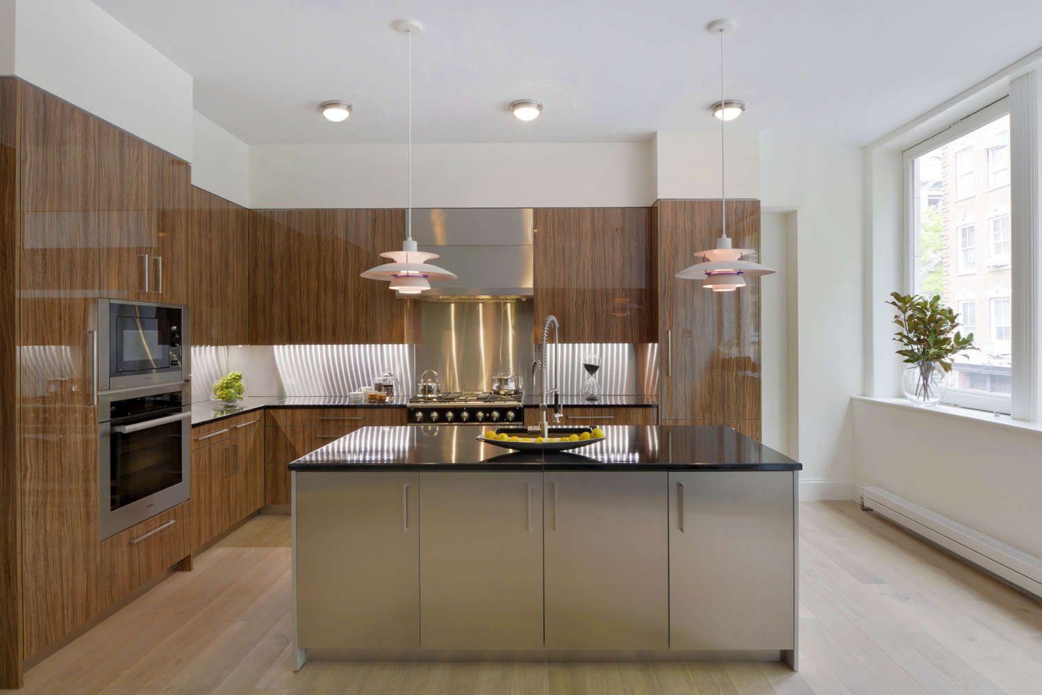 NYC L-shaped loft kitchen features flat panel, frameless fully custom Artcraft cabinetry in a mix of high gloss olivewood and brushed alumasteel, light oak floording and black granite countertops. Design by Randy O'Kane, CKD, of Bilotta Kitchens.
