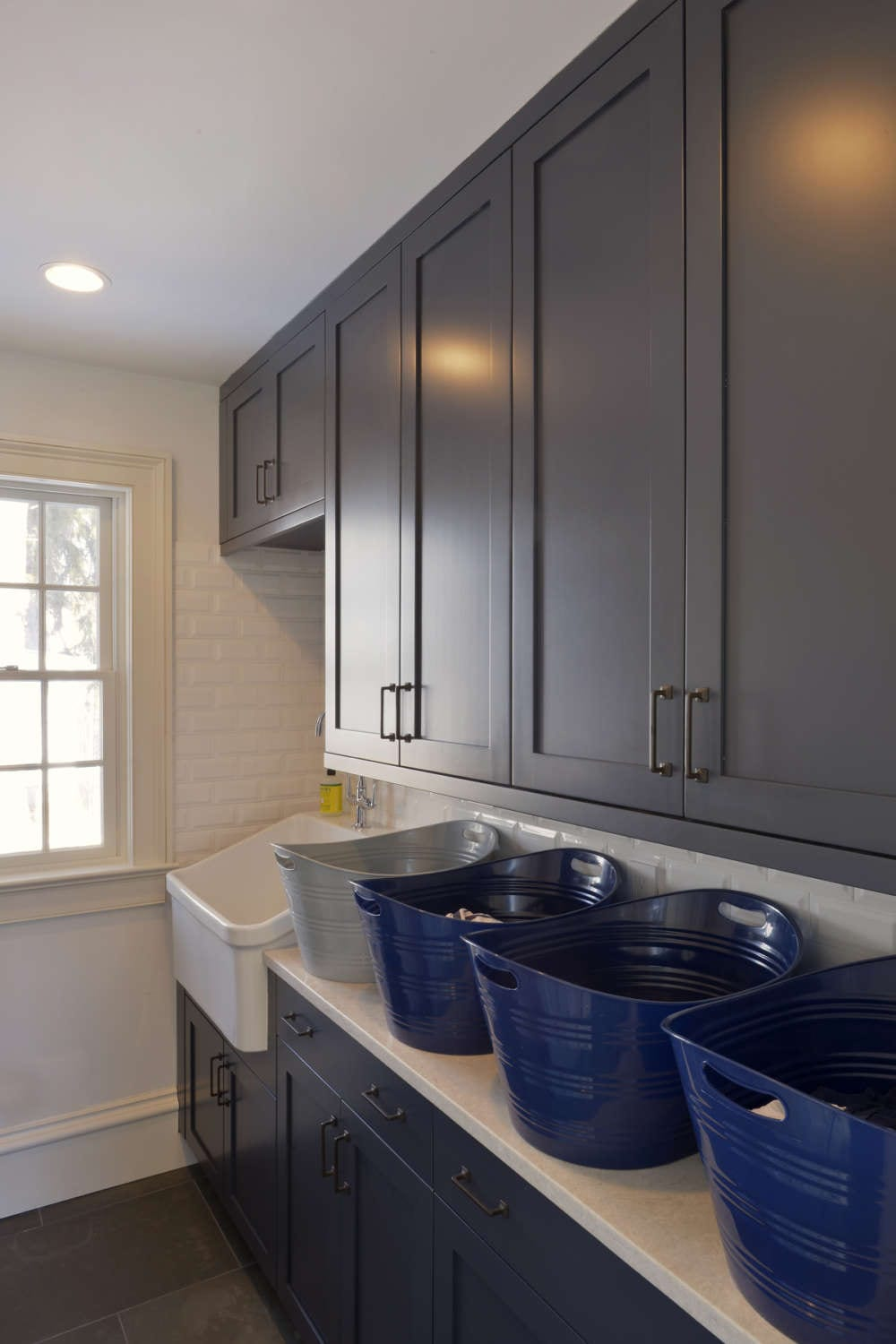 White tiled laundry room features dark blue painted shaker style, frameless Bilotta cabinetry with brushed stainless hardware, white quartz countertop and a large white laundry sink. Design by Paulette Gambacorta of Bilotta Kitchens.