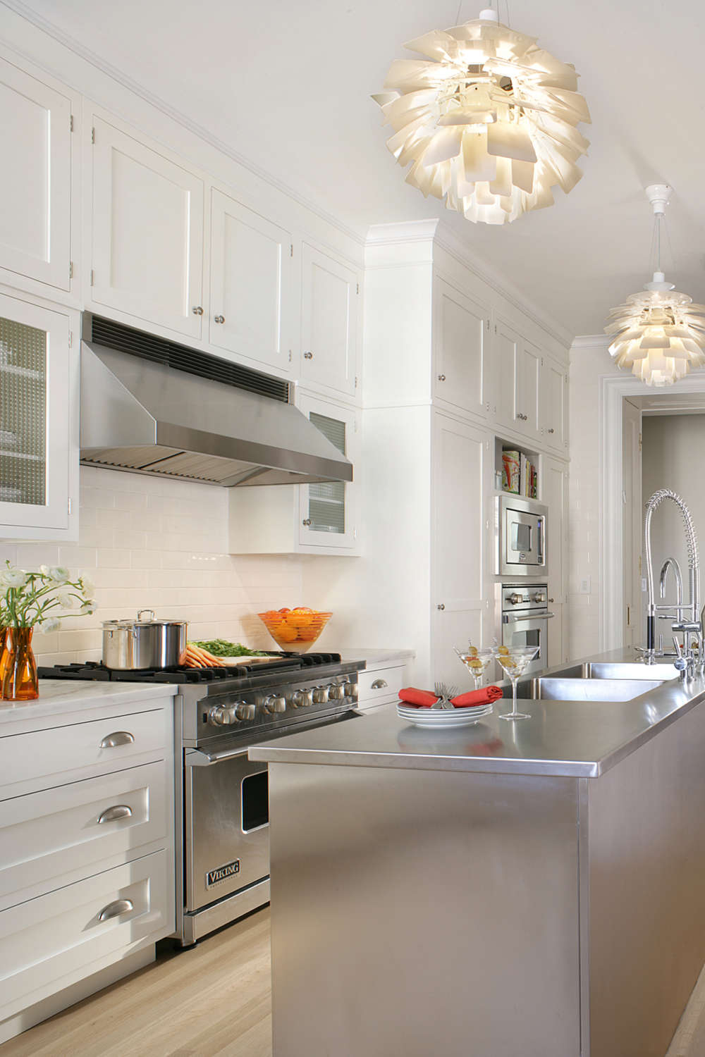 Transitional galley kitchen features white painted, shaker style, double stacked handcrafted cabinets by Rutt with Bendheim glass inserts, and stainless steel island with countertop. White modern flower pendant lights accent the room. Design by Randy O'Kane, CKD, of Bilotta Kitchens.