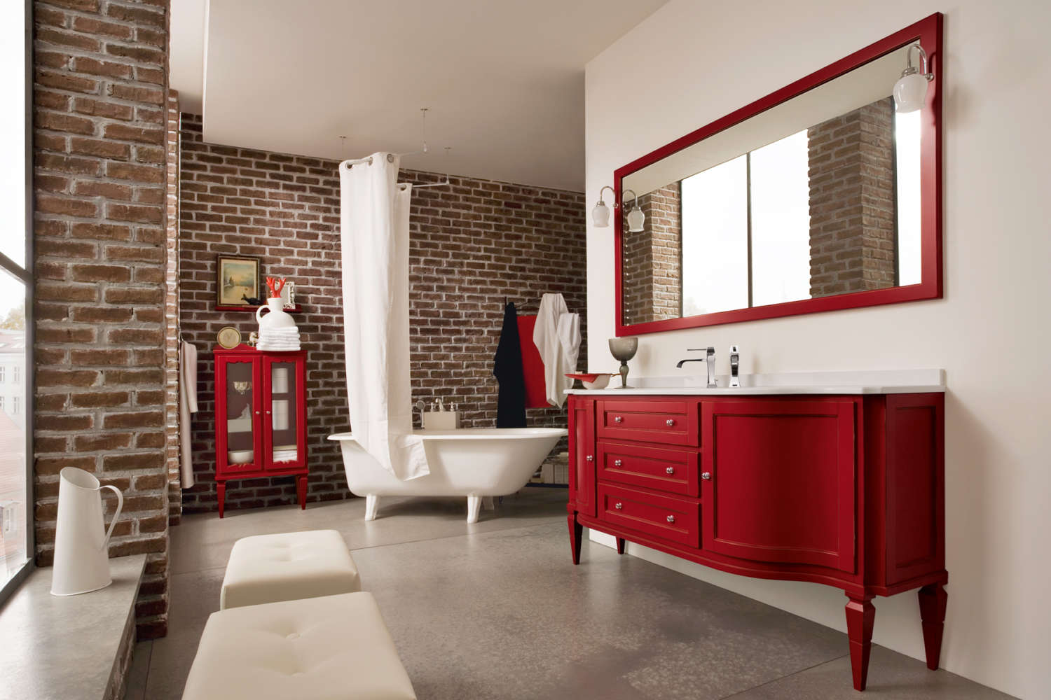 A red painted freestanding vanity on legs by Cerasa Cabinetry with polished silver door pulls and white quartz top is the focal point of this contemporary bath. Additional features are the large red framed mirror above the vanity, red painted storage cabinet with legs and glass front doors by Cerasa Cabinetry, and white slipper tub. The bathroom features exposed brick walls and oversized windows. Design by Jeff Eakley of Bilotta Kitchens.