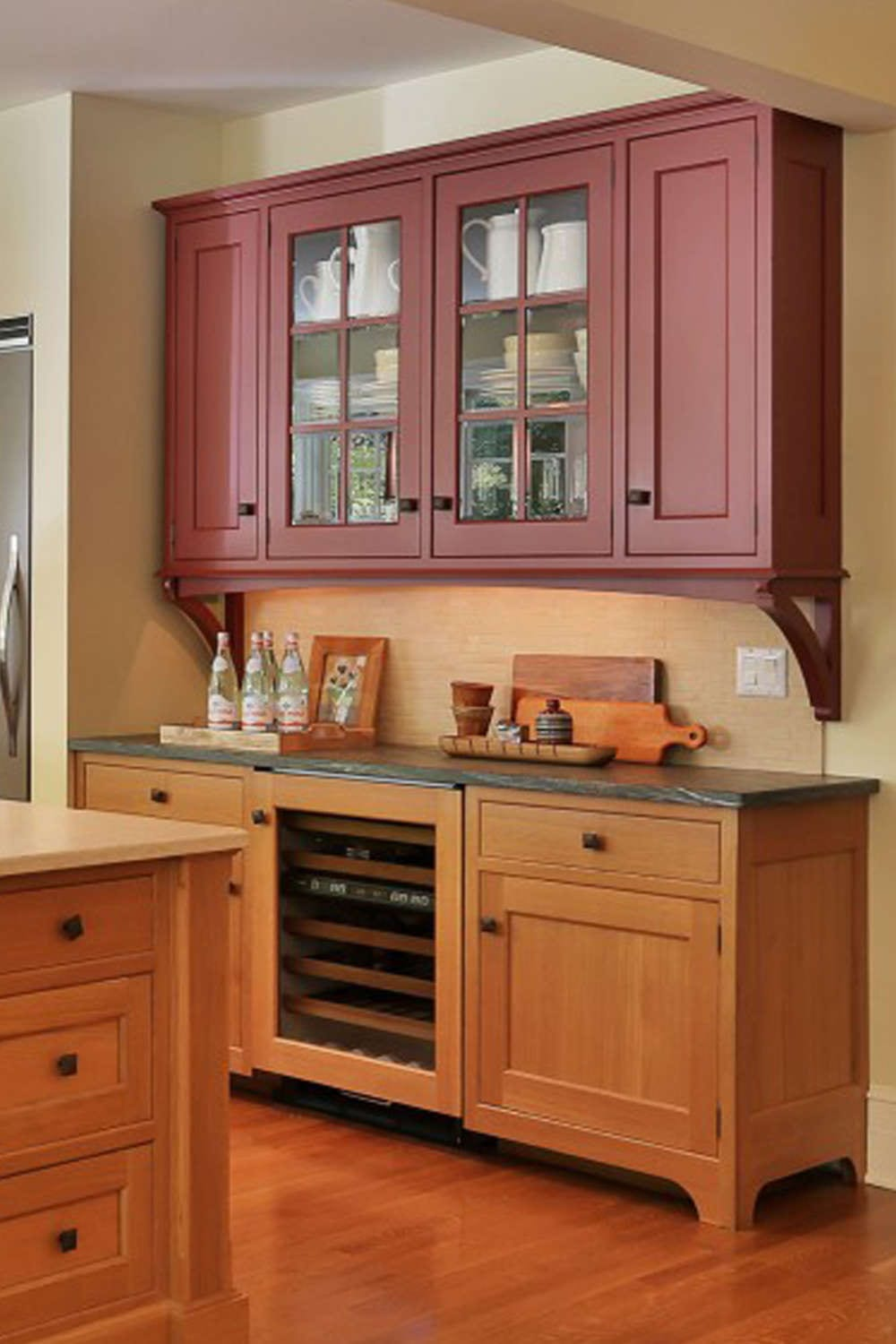 Warm Craftsman style kitchen features a custom shaker style red brink painted hutch by Rutt Handcrafted Cabinetry. The kitchen also incorporates Rutt shaker style cabinets in a mix of rift cut white oak and custom red brick paint finish, square oil rubbed bronze hardware and a mix of green soapstone and warm toned granite countertops. Design by Randy O'Kane, CKD, of Bilotta Kitchens.