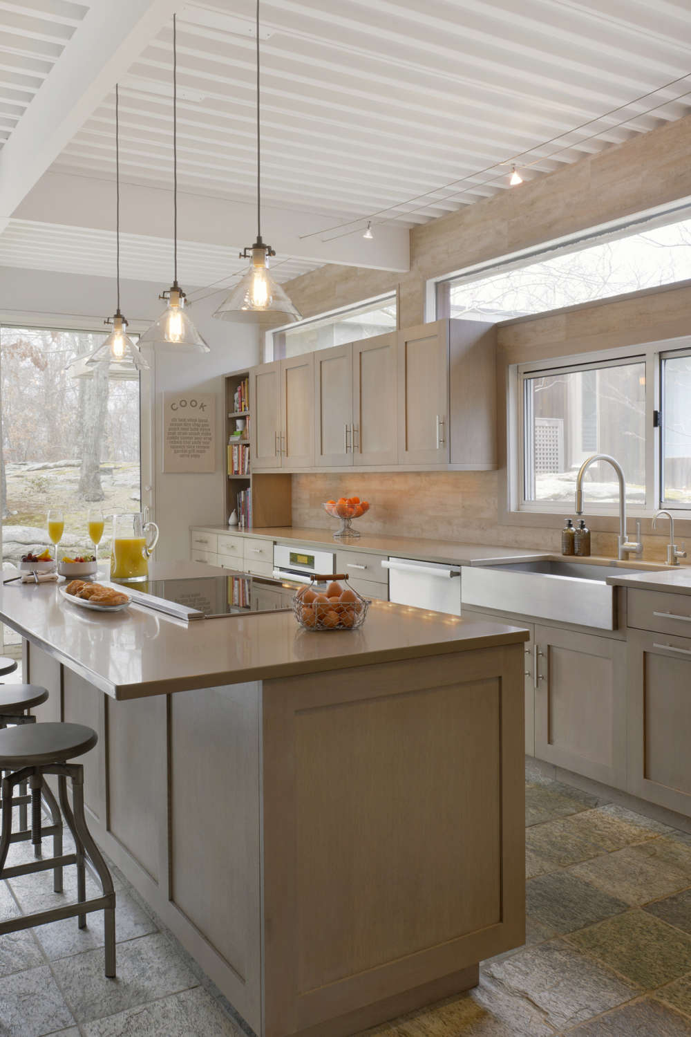 Rustic kitchen is flooded with light from sliders, transon windows and the industrial pendant lights over the island. Kitchen blends neutral quartz counters with soft travertine backspash and floor tiles and frameless, shaker style rift cut white oak Bilotta cabinets with Driftwood stain. Design by Danielle Florie of Bilotta Kitchens.
