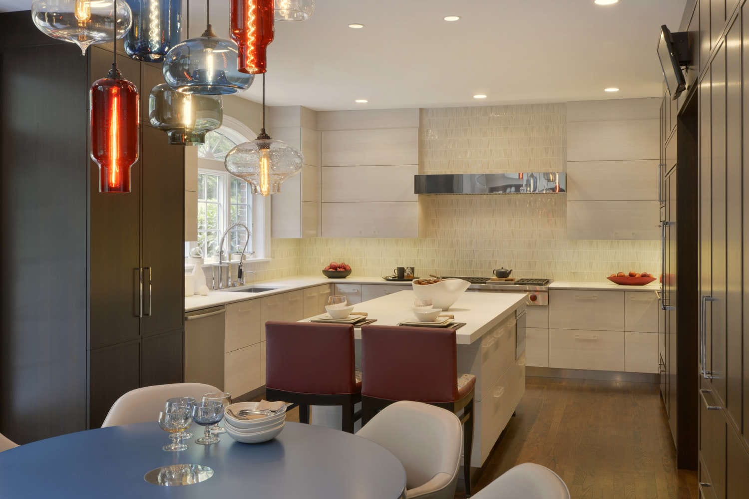 U-shaped kitchen features a center island and eat-in breakfast nook and fully custom, frameless Artcraft Cabinetry in a mix of flat panel with white textured laminate and shaker style in walnut. Red accents appear in the leather stools at the island and the pendant lights over the breakfast nook. Design by RitaLuisa Garces of Bilotta Kitchens.