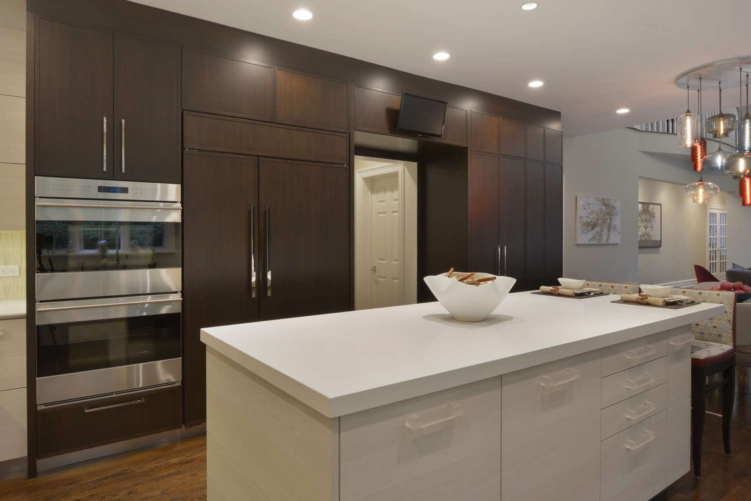 U-shaped kitchen features a mix of flat panel white textured laminate and shaker style walnut fully custom cabinets by Artcraft. The kitchen has white quartz countertops throughout, oak flooring, and a mix of chrome and red accents. Design by RitaLuisa Garces of Bilotta Kitchens.