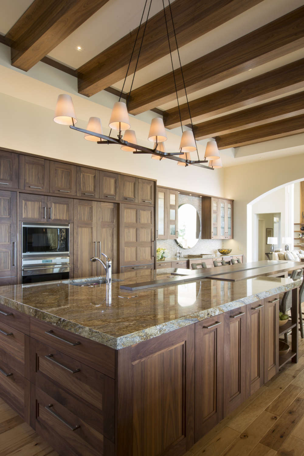 Transitional kitchen features high ceilings with exposed beams, fully custom natural walnut, frameless shaker style Rutt Regency Cabinetry, a large island with seating and warm-toned polished granite countertops. Design by RitaLuisa Garces of Bilotta Kitchens.