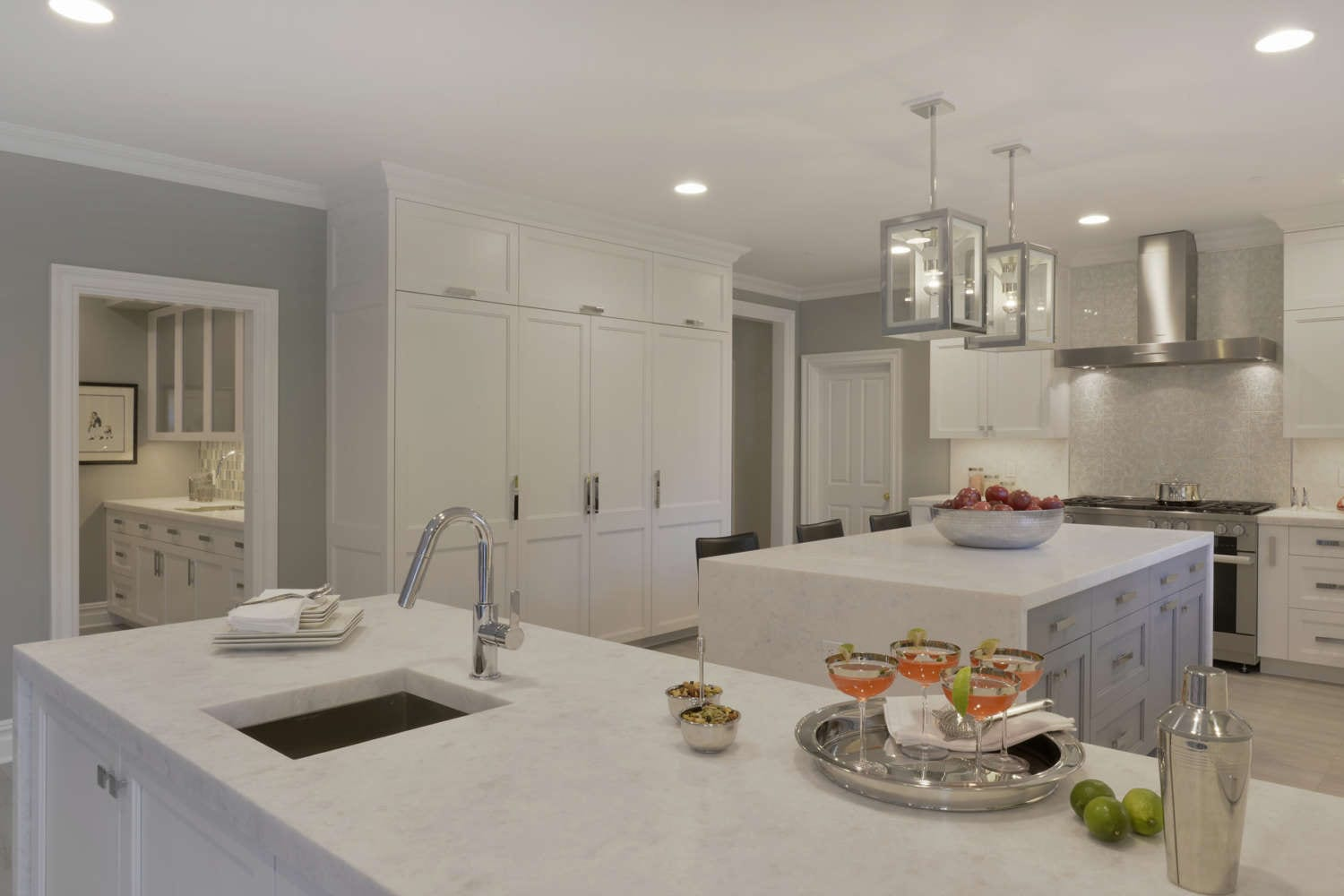 The island of this all white kitchen features a marble waterfall countertop and seating, and is lit by silver pendant lights. The kitchen design by Danielle Florie of Bilotta Kitchens features fully custom frameless shaker style double tiered white painted Bilotta Cabinetry with open corner shelves and polished stainless accents.