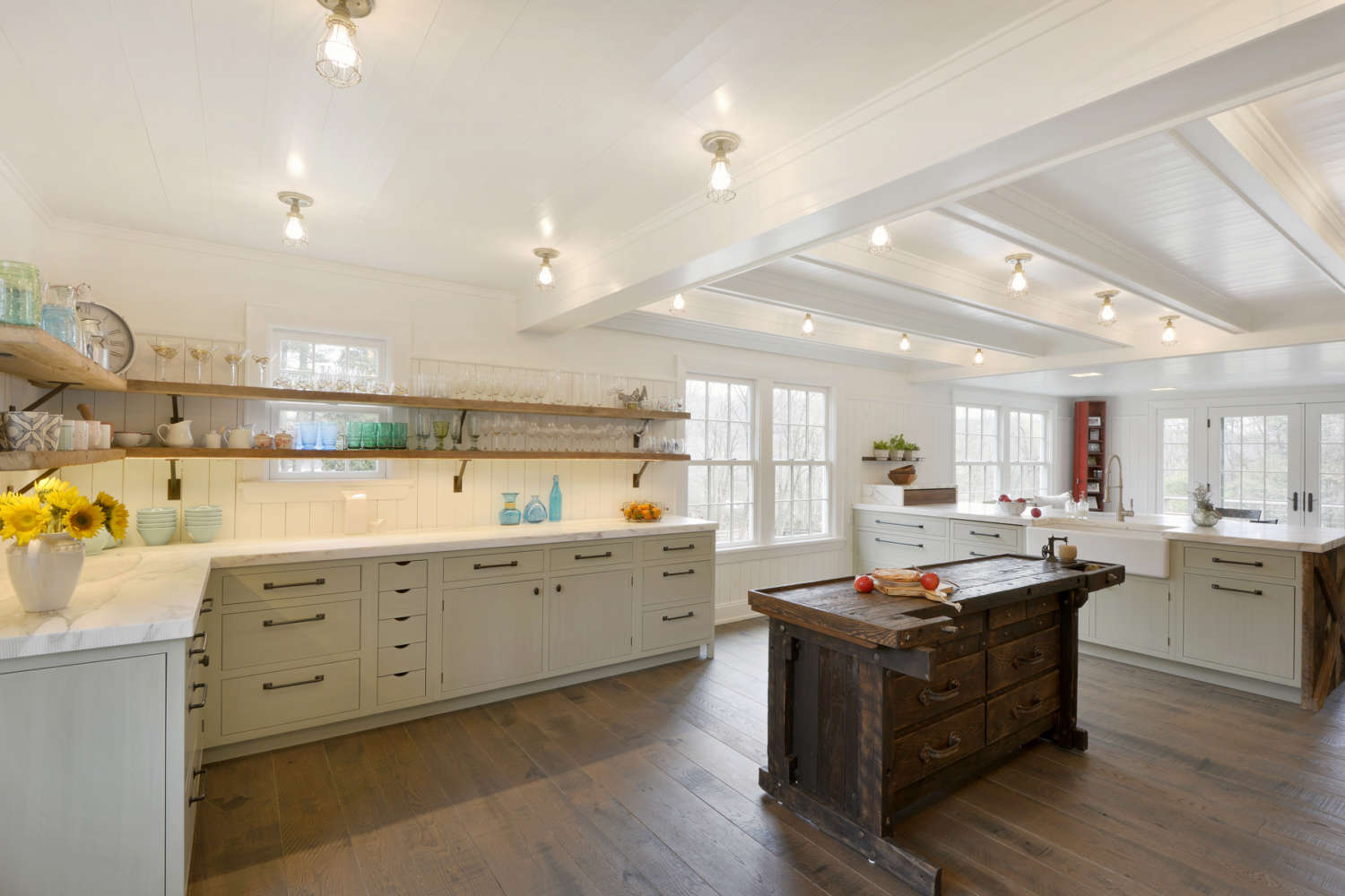 Expansive country kitchen features wood plank flooring, white beadboard ceiling and walls, exposed lighting, oversized windows, a custom wood island, fully custom flat panel inset pale green painted cabinets by Bilotta and white marble countertops. The kitchen design by Paulette Gambacorta of Bilotta Kitchens includes accents of oil rubbed bronze in the cabinet hardware and the supports for the open shelving.