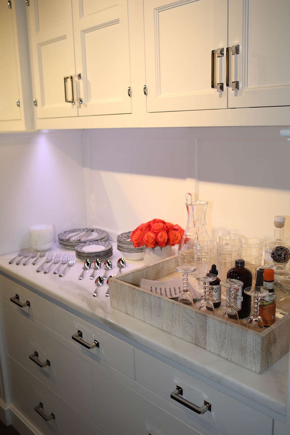 Wet bar area with white painted shaker style cabinets, white quartz counter and robust stainless hardware.