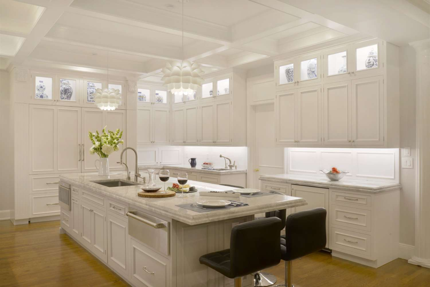 Lit upper cabinets, under cabinet lighting and white flower pendant lights help this large transitional kitchen glow. Fully custom white painted Bilotta cabinetry.