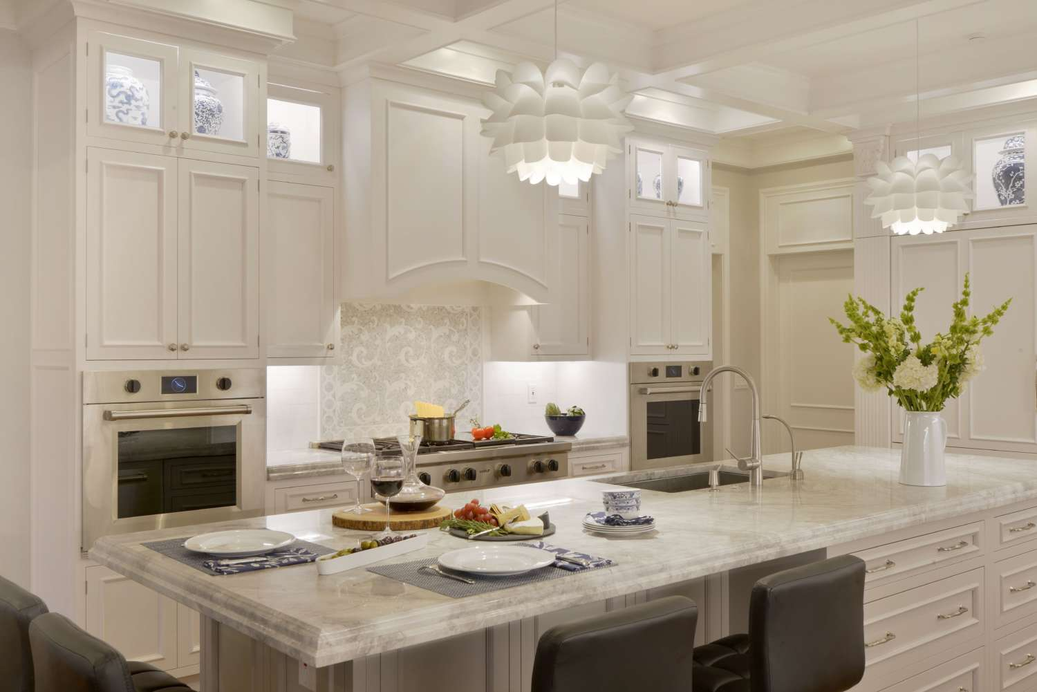 Well-lit transitional kitchen with coffered ceiling, white painted custom cabinets and elegant marble-topped island.