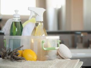 Container of kitchen cleaning products: spray bottles, soap lemon and lavender.