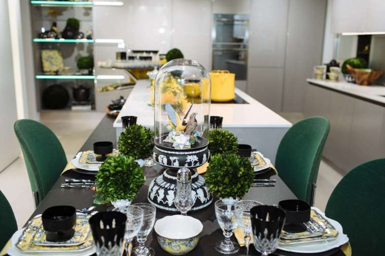 table set with yellow and black toile china, black cut crystal and mini boxwoods