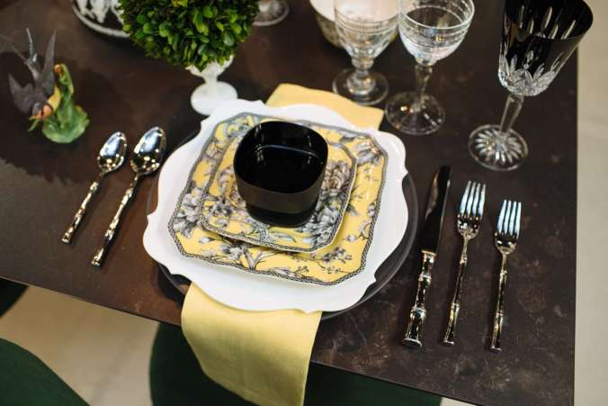 toile-style place setting of black florals and birds on yellow, called Adelaide yellow, by 222 Fifth coupled with yellow napkins and bamboo shaped flatware